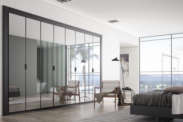 Armario a medida con puertas batientes lisas en espejo plata.