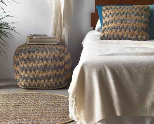 Alfombra de fibra vegetal con diferentes colores tamaños en forma cuadrada o redonda. Pouff tapizado en fibra vegetal. Percha de pared para colgar de madera con pomos.