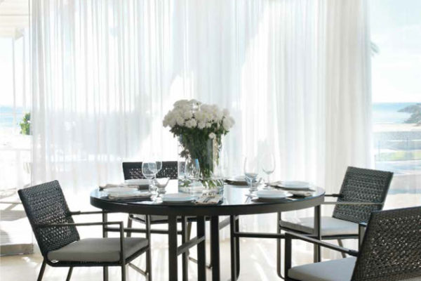 Mesa de comedor redonda para exterior en aluminio y cristal.