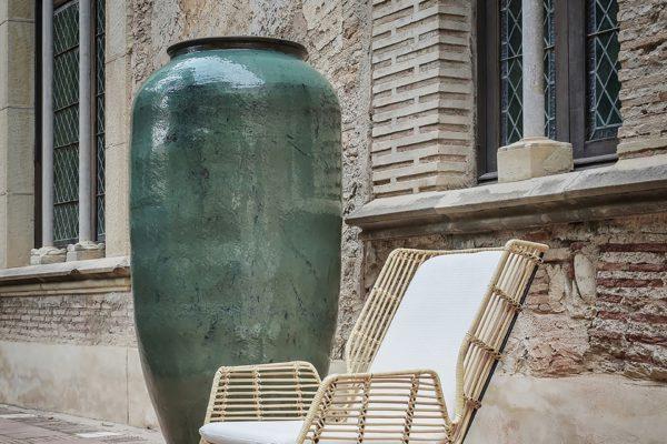 Vasija de cerámica en verde brillo y sillón en ratán y patas de hierro tapizado en blanco.