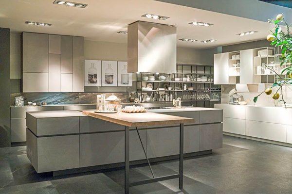 Cocina a medida con zona de estantería metálica, isla central con mesa volada de madera con patas de metal.