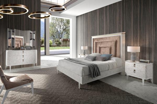 Dormitorio Umbito, compuesto por cama tapizada con bañera, mesitas de dos cajones con patas, cómoda y espejo a juego. Acabado laca alto brillo.