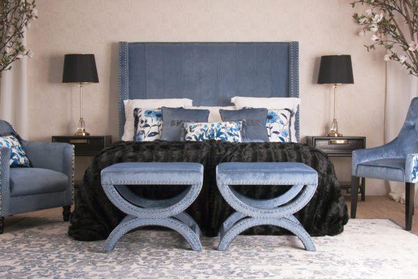 Dormitorio con cabecero con orejas tapizado en terciopelo azul, mesitas estilo oriental lacadas en negro envejecido, banquetas  y butacas tapizadas en terciopelo azul.