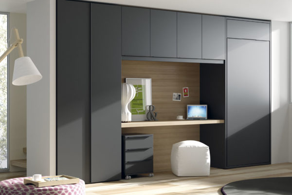 Dormitorio juvenil compuesto por cama abatible vertical, armario a medida, escritorio y módulos con puerta en la parte superior.
