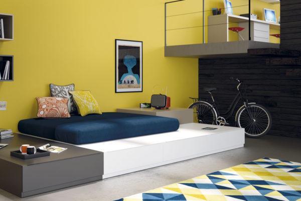 Dormitorio juvenil compuesto por cama compacta y estanterias a pared.