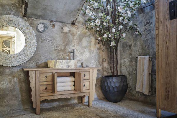 Mueble toallero para aseo en madera envejecida. Pila de piedra. Espejo madera envejecida. Macetero con formas y relieves en negro con planta artificial gigante.
