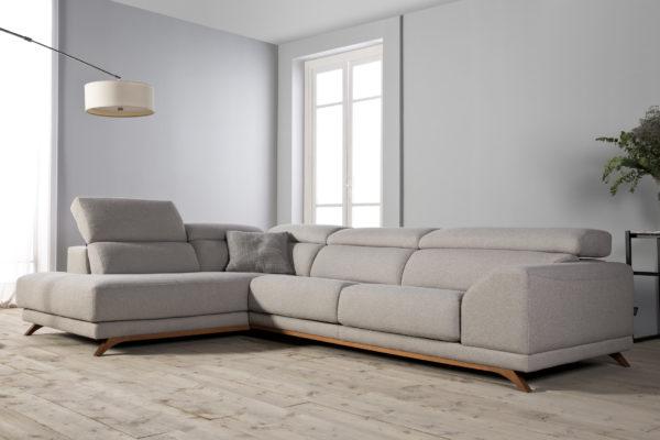 Sofà amb chaise longue i respatller reclinable. Potes de fusta i entapissat beig.