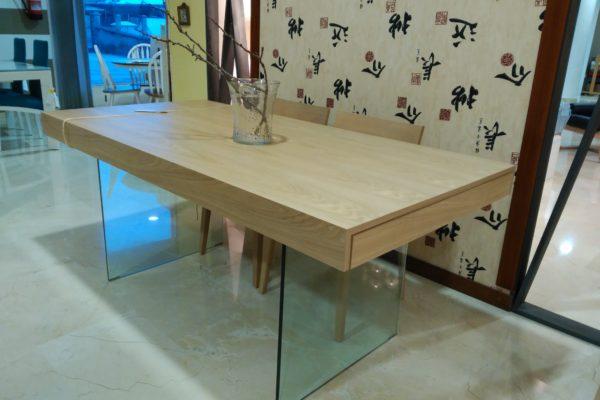 Mesa de comedor de 90x180cm con dos extensiones en madera de fresno natural y pies de cristal.