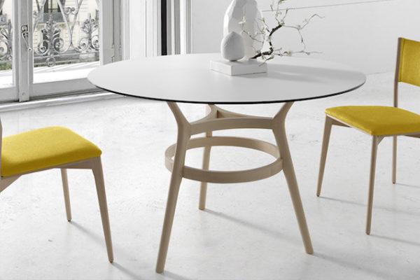 Mesa de comedor redonda, pie figura en madera y tapa de cristal. Sillas de madera con respaldo y asiento tapizado.