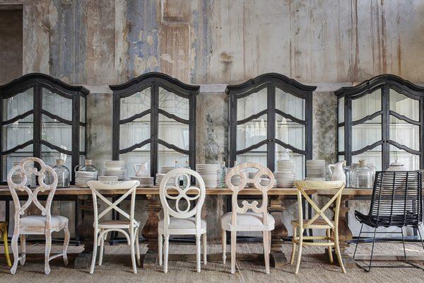 Mesa comedor con patas columna de madera. Sillas de varios modelos. Vitrina con patas de madera lacada negro envejecido.
