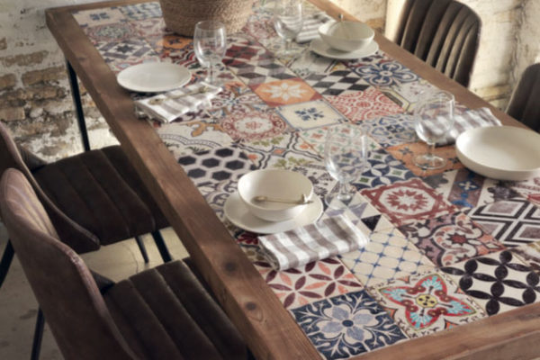 Mesa comedor fija rectangular con incrustaciones de cerámica, madera envejecida y patas metálicas. Sillas metal y polipiel estilo industrial.